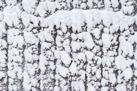 Snow on the fence. Winter natural snow background.