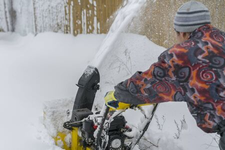 man operating snow blower to remove snow on driveway. Man using a snowblower. A man cleans snow from sidewalks with snowblower. Reklamní fotografie - 133998860