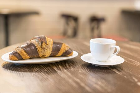 Chocolate croissant on a plate in a cafe and a cup of espresso.