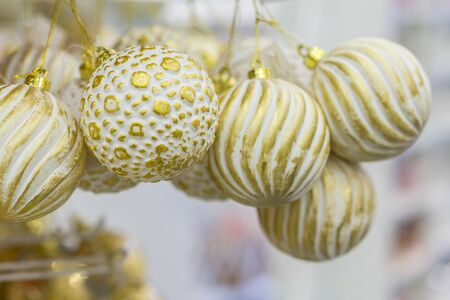 Yellow Christmas balls in a New Years store. Christmas toys background for a Christmas card, Christmas wallpapers. Banco de Imagens