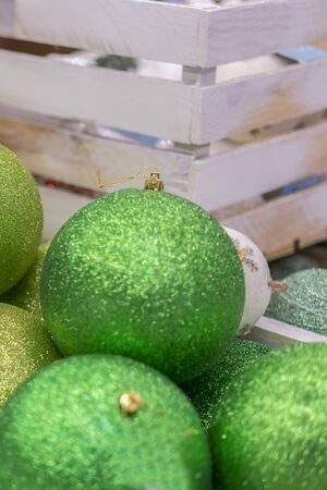 Green Christmas decorations in box. Colorful baubles in the white box. vertical photo.