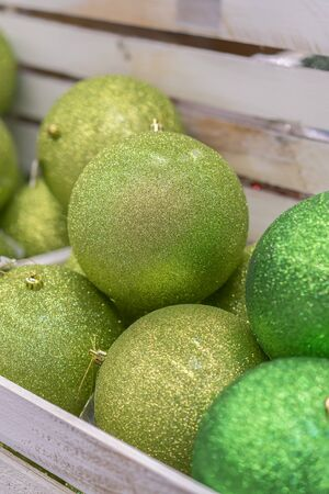 Green and gold Christmas decorations in box. Colorful baubles in the white box. vertical photo.
