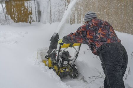 man operating snow blower to remove snow on driveway. Man using a snowblower. A man cleans snow from sidewalks with snowblower. Reklamní fotografie - 133999261