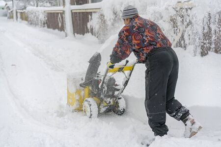 man operating snow blower to remove snow on driveway. Man using a snowblower. A man cleans snow from sidewalks with snowblower. Banco de Imagens