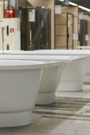 White bathtubs in a hardware store. The concept of choosing and installing bathtubs. vertical photo. Stock fotó - 133999339