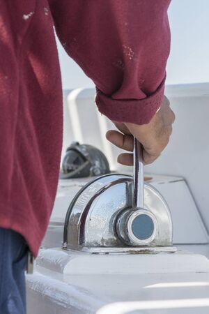 A man drives a yacht. close-up. vertical photo.