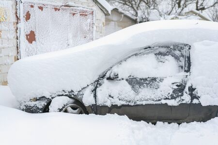 Snow-covered machine. Car under the snow. Lots of snow and big snowdrifts on the street. Vehicles are completely covered in snow. Cold winter weather.