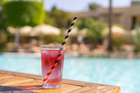 Red cocktail with ice with a straw on the background of the pool.
