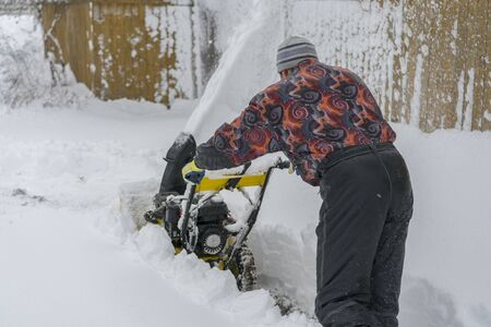 man operating snow blower to remove snow on driveway. Man using a snowblower. A man cleans snow from sidewalks with snowblower. Stock fotó - 134654928