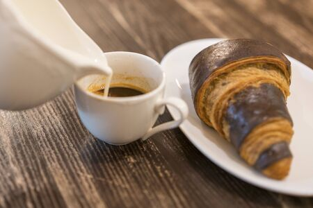 Cream is poured into coffee. Croissant on a table in a cafe. Breakfast concept. Stock fotó - 134655116