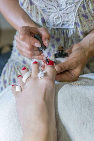 pedicure process macro closeup. pedicure process and spa procedure macro closeup. Master does pedicure for client. Pedicure process. Girl draws toenails. vertical photo. Stok Fotoğraf