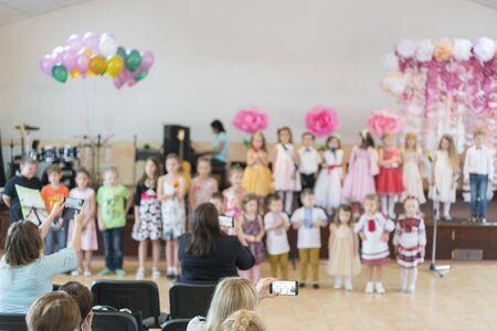 Children's party in primary school. Young children on stage in kindergarten appear in front parents. Holiday in kindergarten. blurry. Stock fotó - 134656457