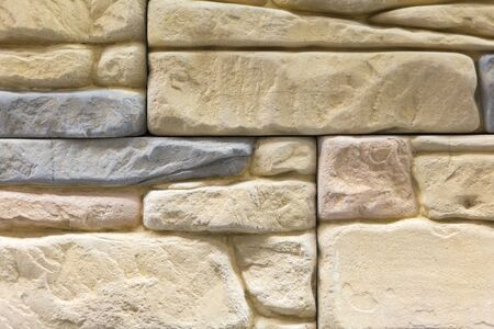 Light brown wall made of decorative stone. Beige stone for decoration. background.