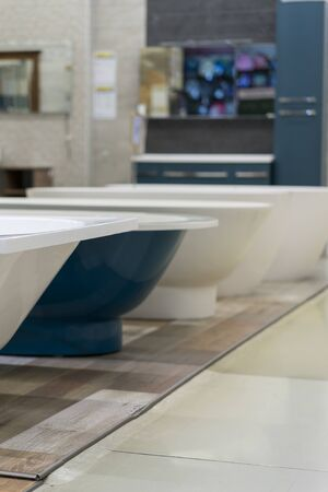 White and blue bathtubs in a hardware store. The concept of choosing and installing bathtubs. vertical photo. Stock fotó