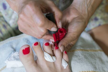 Master does pedicure for client. Pedicure process. Girl draws toenails. Stock fotó
