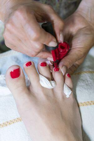 pedicure process macro closeup. pedicure process and spa procedure macro closeup. Master does pedicure for client. Pedicure process. Girl draws toenails. vertical photo. Stock fotó