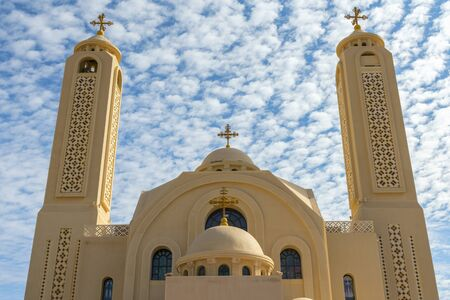 Coptic Orthodox Church in Sharm El Sheikh, Egypt.Against the backdrop of a beautiful sky with clouds. All Saints Church. Concept of the righteous faith.