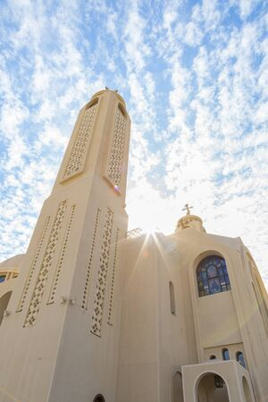 Coptic Orthodox Church in Sharm El Sheikh, Egypt.Against the backdrop of a beautiful sky with clouds. All Saints Church. Concept of the righteous faith. vertical photo. Stock fotó