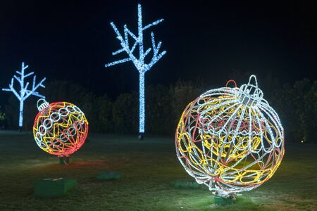 Large luminous Christmas ball on a green flowerbed. A very large and walkable Christmas ball as a decoration for the Christmas season with many fairy lights.
