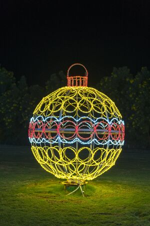 Large luminous Christmas ball on a green flowerbed. A very large and walkable Christmas ball as a decoration for the Christmas season with many fairy lights. Stock fotó - 134657150