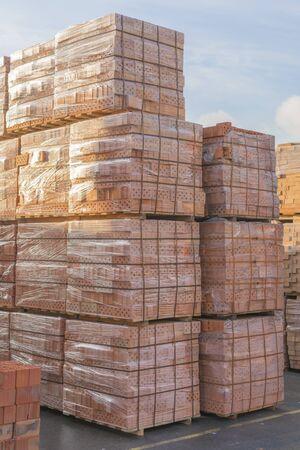 Several pallets with concrete brick stacked on top of each other in depot. Industrial production of bricks. vertical photo