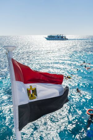 Egypt national flag waving on the wind of blue sky background. White yachts tourists in azure water Red sea, Arab Republic of Egypt. Tourists swim in the clear sea. Vertical photo.