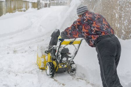 man operating snow blower to remove snow on driveway. Man using a snowblower. A man cleans snow from sidewalks with snowblower. Stock fotó