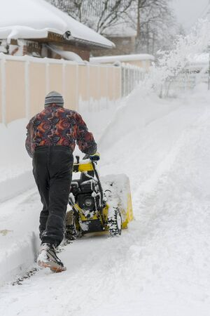 man operating snow blower to remove snow on driveway. Man using a snowblower. A man cleans snow from sidewalks with snowblower. Vertical photo.
