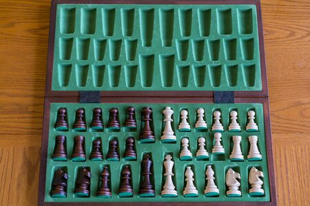 A wooden chess set in its box, view from above with brown background. The picture shows old traditional hand-made chess in a box.