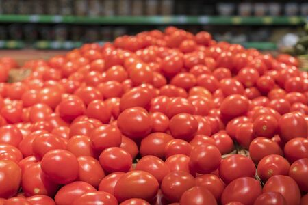 Vegetables are full of vitamins. Fresh and ripe tomatoes in a basket on a supermarket shelf. Ripe tomatoes in a supermarket. Stock fotó