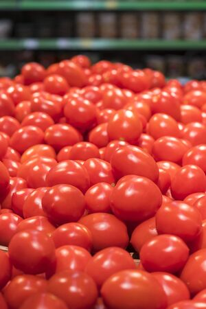 Vegetables are full of vitamins. Fresh and ripe tomatoes in a basket on a supermarket shelf. Ripe tomatoes in a supermarket. vertical photo.