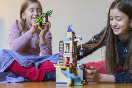 Two little sisters are playing childrens constructor at home. selected focus. Stock fotó