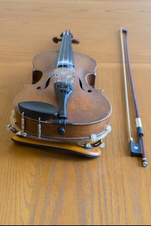 violin lying on a wooden textured table. Violin body and bow on wood table with golden glow. Top view. Horizontal composition. vertical photo.