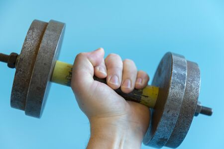 Male hand is holding a dumbbell on a blue background. lose up. Stock fotó