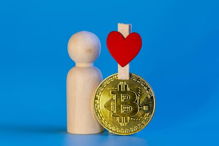 Human figurine, bitcoin coin and heart on a blue background. love for cryptocurrency concept.