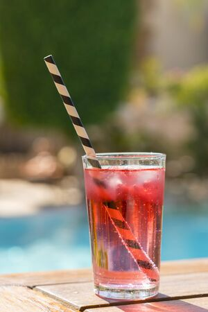 Red cocktail with ice with a straw on the background of the pool. vertical photo. Stock fotó