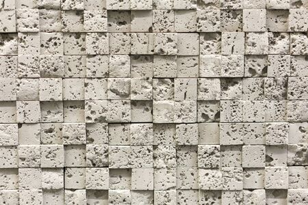 Square beige pebbles for decoration. Stone background.
