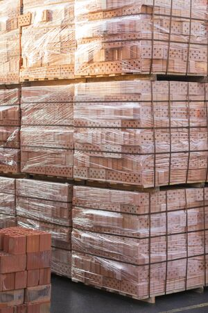 Several pallets with concrete brick stacked on top of each other in depot. Industrial production of bricks. vertical photo. Фото со стока