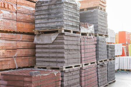 pallets with bricks in the building store. Racks with brick. Masonry, stonework. Several pallets with concrete brick stacked on top of each other in depot. new bricks on pallets.