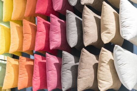 Multi-colored pillows background. Creative background made of pillows. Pink red yellow gray and beige pillows. vacation concept.
