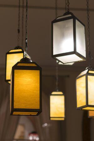 Creative yellow lanterns in the lobby. vertical photo. Фото со стока
