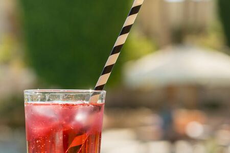 Red cocktail with ice with a straw on a on bar background.