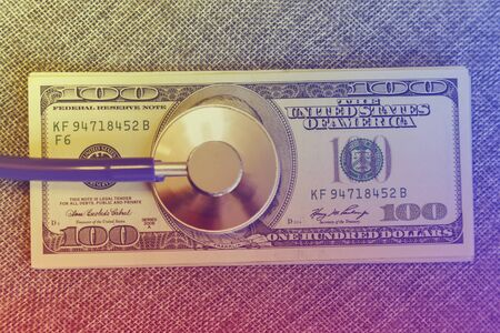 Financial checkup: Stethoscope on pile of U.S. hundred dollar bill on grey background. financial wellness. toned. Фото со стока
