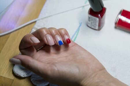 Female hand with beige blue and red varnish. The concept of choosing nail polish. Stock fotó - 138046640