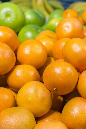 Fresh oranges in the store. Close up view of madarines orange on the sheft in the supermarket. Healty and fresh fruits background in a supermarket super store. vertical photo. Фото со стока