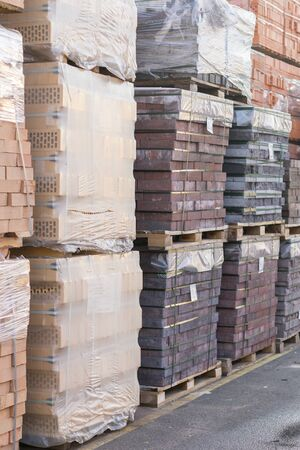 clay brick stored for building construction. Industrial production of bricks. brick production line in factory, stacked bricks. vertical photo. Фото со стока