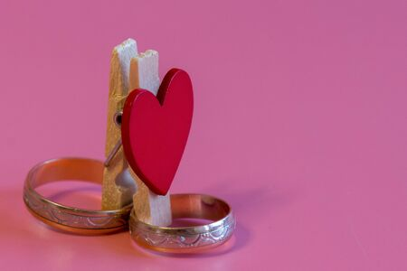 Wedding rings with a heart on a pink background. Love and marriage concept. Close up and top view of golden wedding rings and heart, isolated, copy space. Stock fotó - 138061768