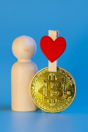 Human figurine, bitcoin coin and heart on a blue background. love for cryptocurrency concept. vertical photo.