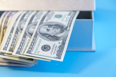 Dollars in a box in the sunlight. Dollars in a box in the sunlight. Open box with dollars.