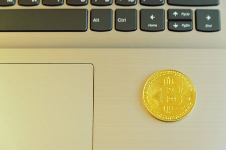 Bitcoin on a laptop. Bitcoin coin symbol on laptop, future concept financial currency, crypto currency sign toned. Фото со стока